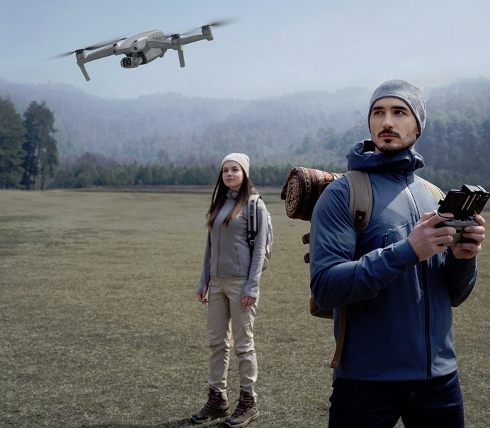 Drohnen-Pilot mit Frau im Hintergrund